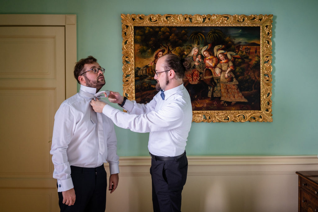 sposo che si prepara per il matrimonio amico cravatta