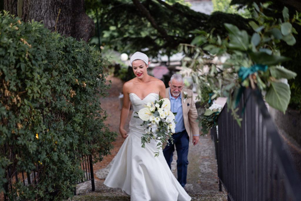sposa che sale le scale con fiori in mano e dietro il padre
